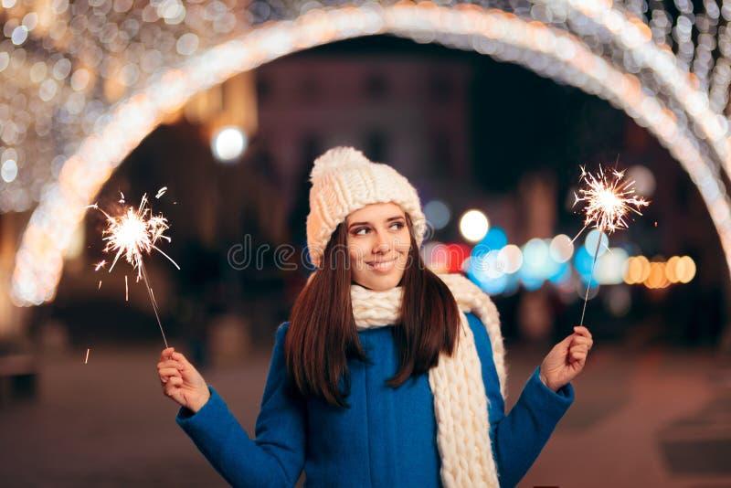 有烟花的快乐的女孩户外庆祝寒假的 图库摄影