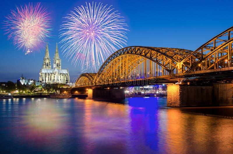 有烟花的科隆大教堂和Hohenzollern桥梁 图库摄影