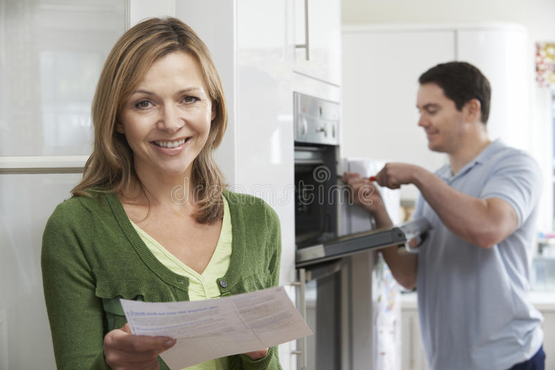有烤箱修理的比尔满意的女性顾客 库存图片
