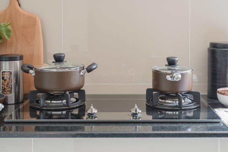 有烤箱的罐在黑花岗岩柜台 图库摄影