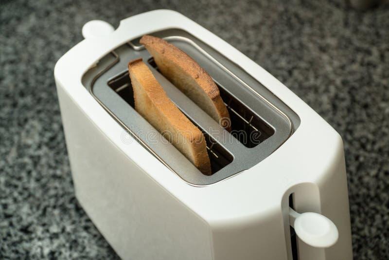 有烤面包片的白色多士炉早餐里面的 灰色桌 免版税库存照片