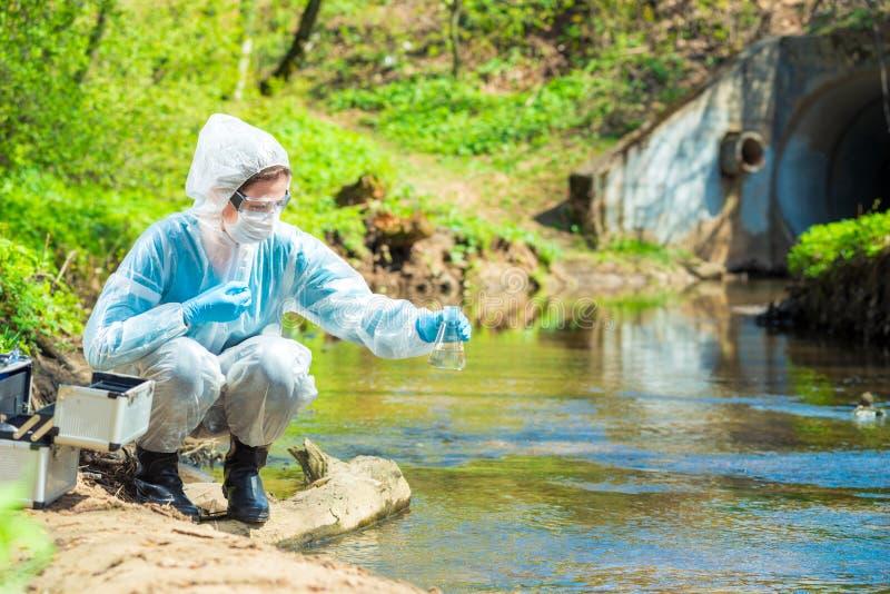 有烧瓶的环境科学家在工业排放站点采取水样品  免版税库存图片