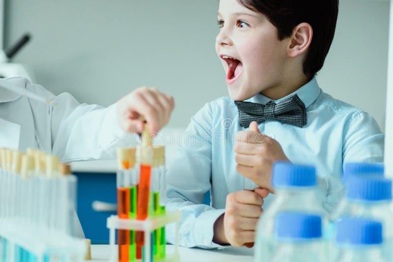 有烧瓶的男小学生在化工实验室,科学学校概念 库存照片