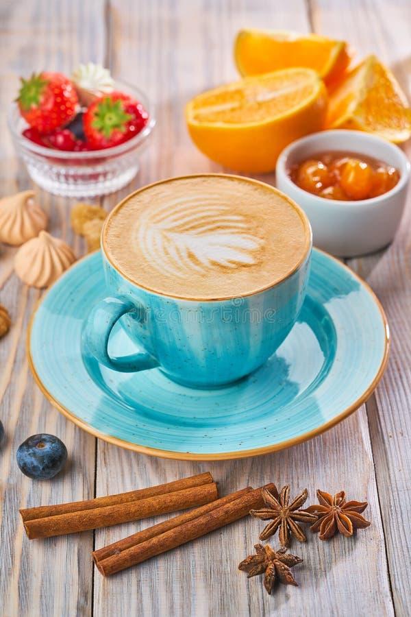 有热奶咖啡、桂香和茴香的蓝色咖啡杯 早餐咖啡概念煎的杯子鸡蛋 免版税图库摄影