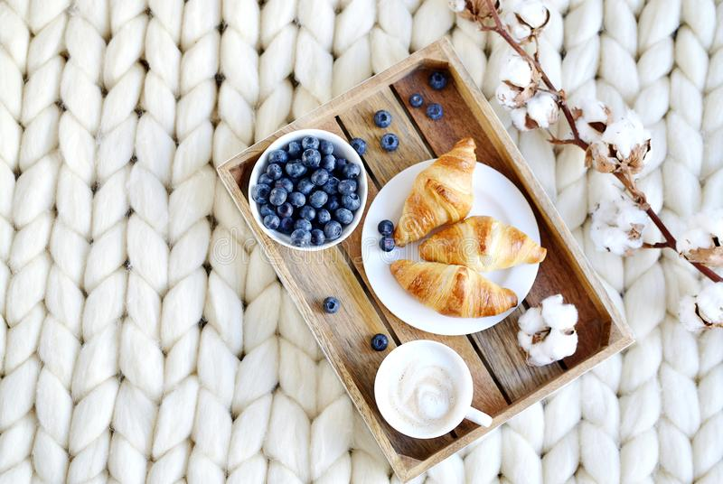 有热奶咖啡和新月形面包的,白色淡色巨型毯子杯 图库摄影
