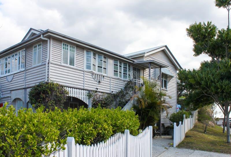 有热带叶子的典型的昆士兰房子和白色尖桩篱栅在阴暗天在澳大利亚 图库摄影
