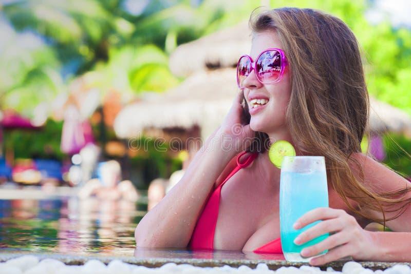 有热带鸡尾酒的美丽的妇女在水池 免版税库存图片