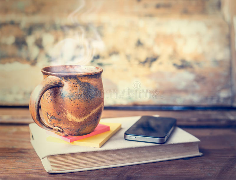 有热的饮料和蒸汽的葡萄酒杯子,发球区域或者咖啡在旧书与智能手机 图库摄影