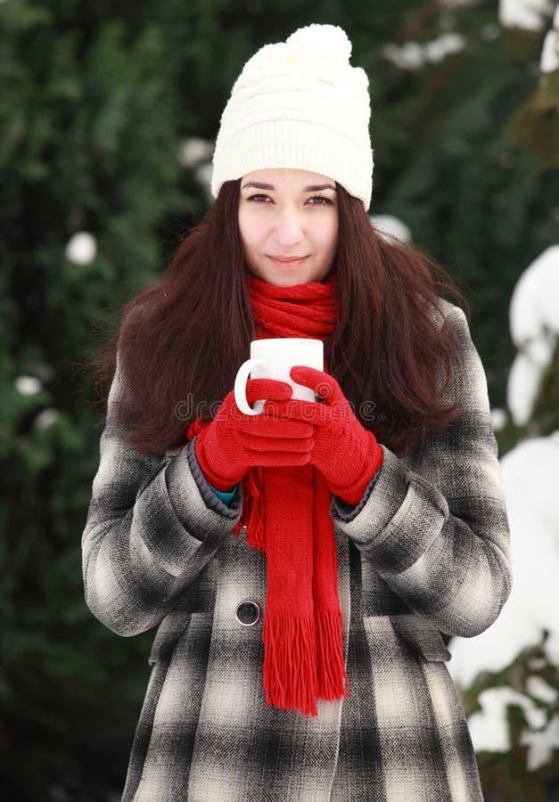 有热的饮料的少妇在室外的冬天 免版税库存图片