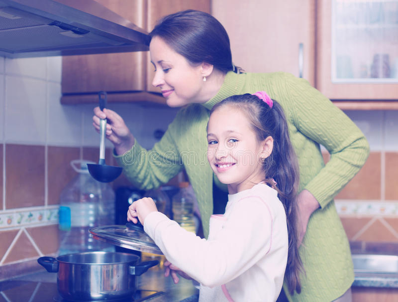有烹调在厨房的女儿的母亲 免版税库存图片
