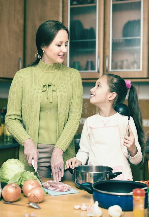 有烹调在厨房的女儿的母亲 免版税库存照片