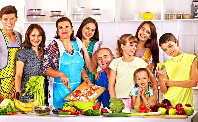 有烹调在厨房的孩子的愉快的家庭。 免版税图库摄影