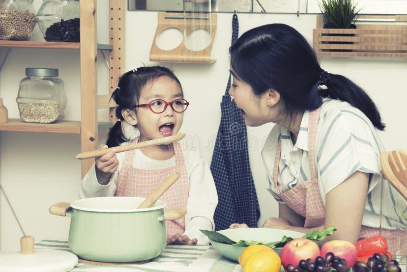 有烹调女儿的厨师的亚裔妈妈妇女在厨房,女孩给妈妈食物大姐妹和妹妹戏剧的用途匙子里  免版税图库摄影