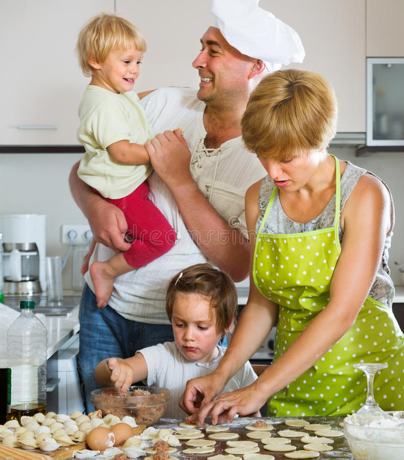 有烹调肉饺子的孩子的愉快的父母 库存照片