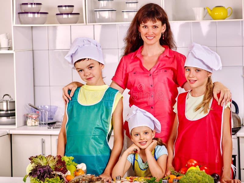 有烹调食物的女儿和儿子的母亲在 库存照片