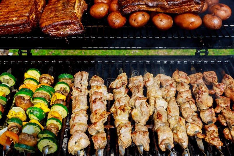 有烹调鸡肉串的煤炭格栅kebab的BBQ用烤晚餐的蘑菇和胡椒 免版税库存图片