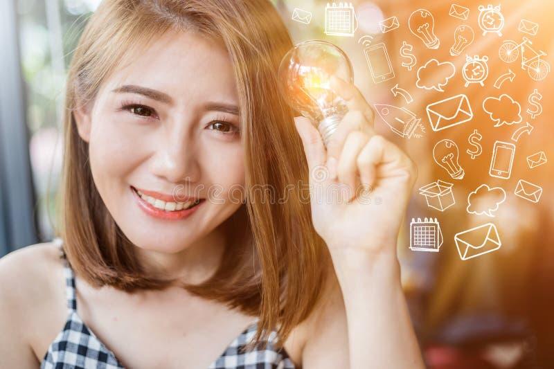 有焕发电灯泡的亚裔聪明的秀丽女孩与lig图画  库存照片