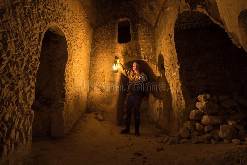 有煤油灯的人探索古老被放弃的地下多白粉洞寺庙 免版税库存照片