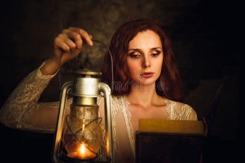 有煤油灯阅读书的美丽的红发少妇 库存照片