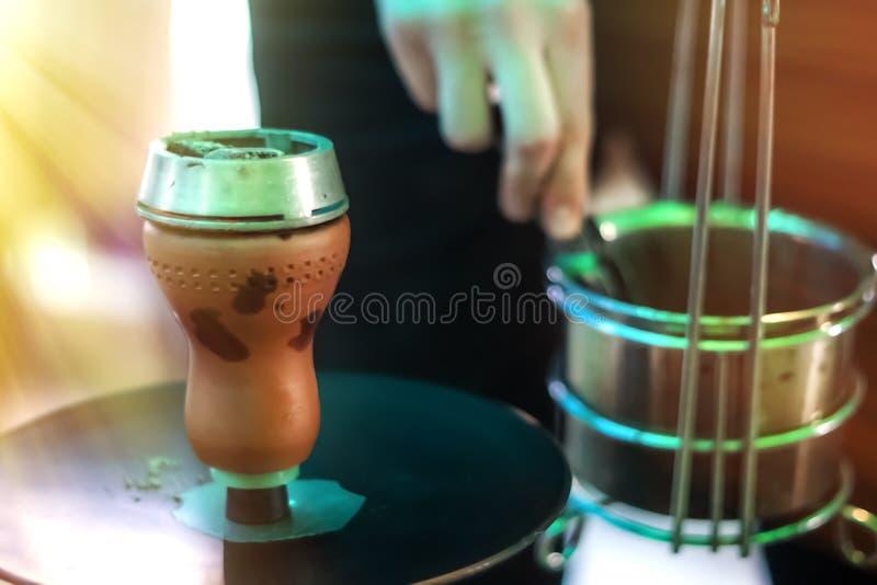 有煤炭的水烟筒碗抽烟的特写镜头的 递拿着shisha水烟筒的镊子并且调整在金属碗的热的煤炭 免版税库存图片