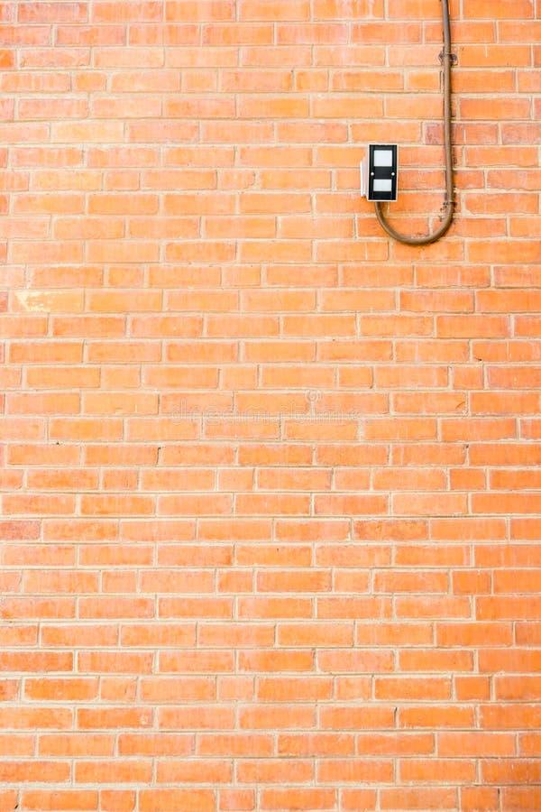 有照明设备绳子的,纹理背景橙色砖墙 免版税库存照片