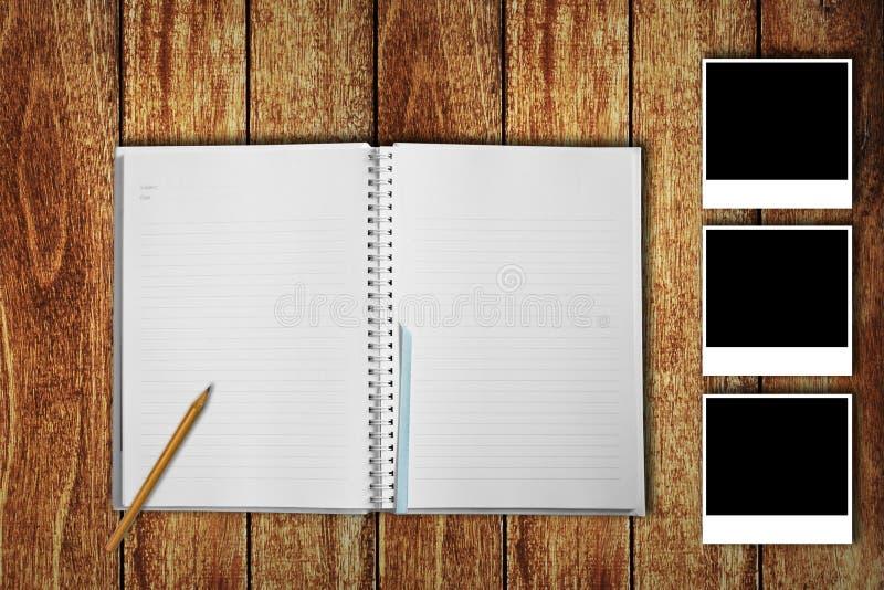 有照片框架的笔记本在木地板上 免版税库存照片