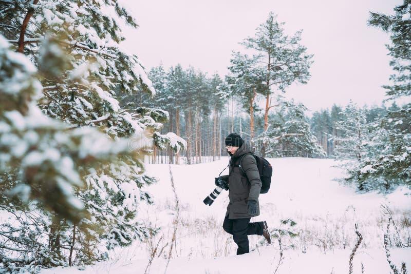 有照片照相机照相的年轻人背包徒步旅行者在冬天斯诺伊森林活跃爱好 走在斯诺伊的徒步旅行者 库存图片