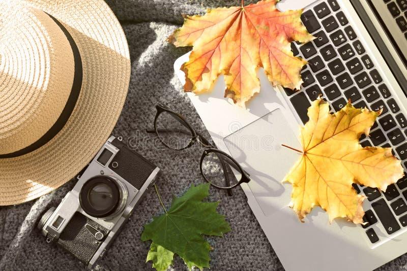 有照片照相机的膝上型计算机和在温暖的格子花呢披肩的秋叶 免版税库存照片