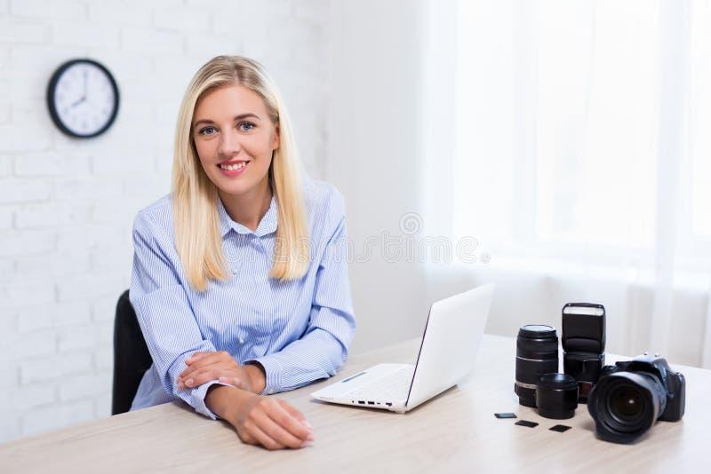有照相机、计算机和运转在办公室的摄影设备的年轻女人专业摄影师 免版税库存图片