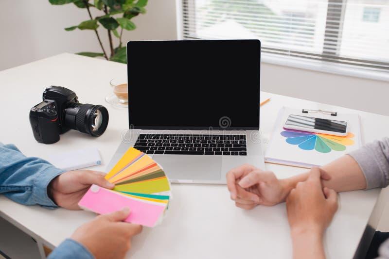 有照相机和手提电脑工作的两位摄影师在办公室 图库摄影