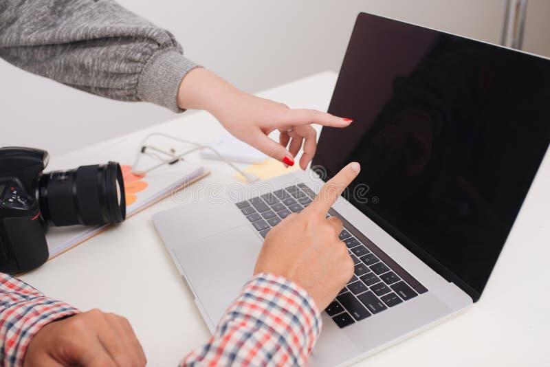 有照相机和手提电脑工作的两位摄影师在办公室 库存照片