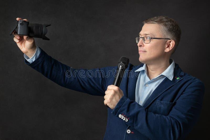 有照相机和无线电话筒的男性博客作者 免版税库存图片