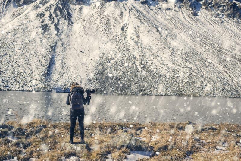 有照相机在一件冬天夹克有毛皮立场的在雪山对面和一个湖的一位妇女摄影师在瑞士 Fluela 免版税库存图片