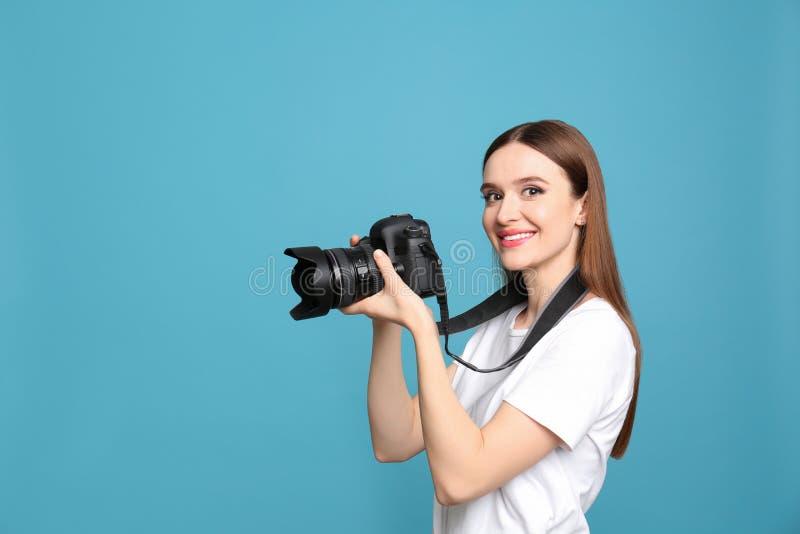 有照相机的专业摄影师在浅兰的背景 免版税库存照片