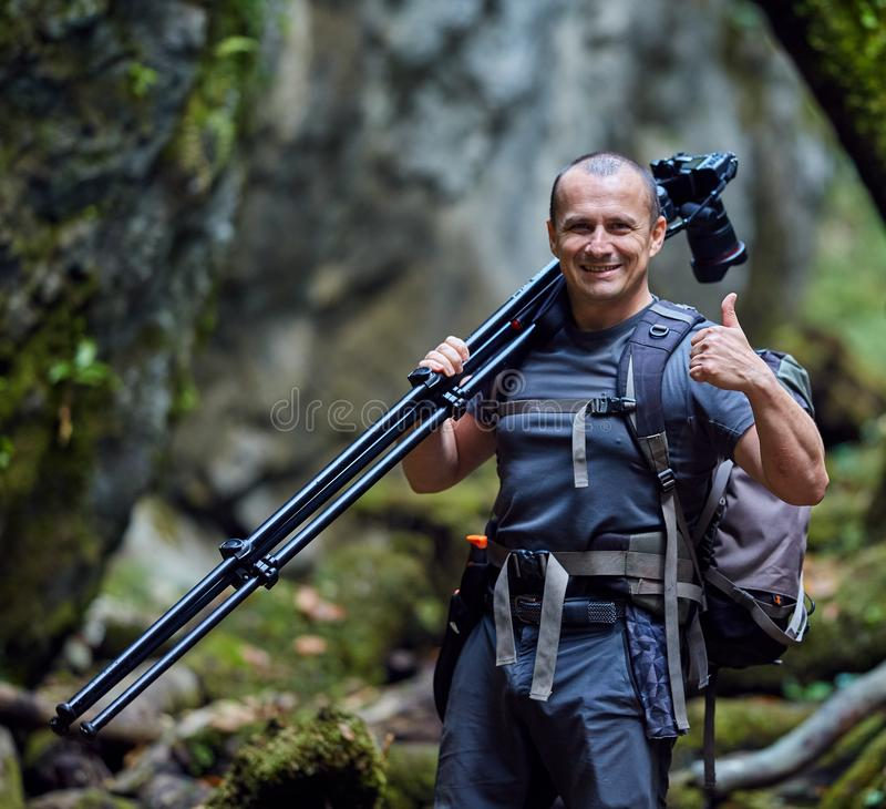 有照相机的专业自然摄影师在三脚架 免版税库存照片