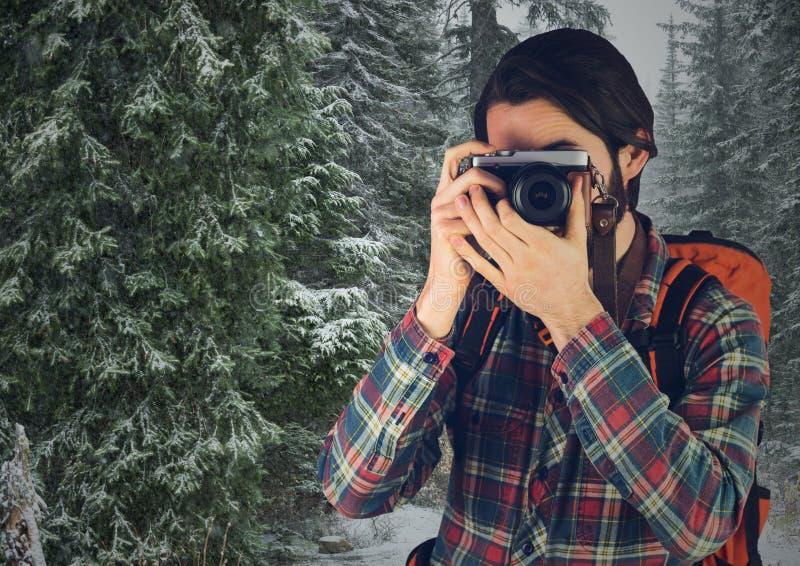 有照相机的千福年的背包徒步旅行者反对多雪的树 免版税库存照片