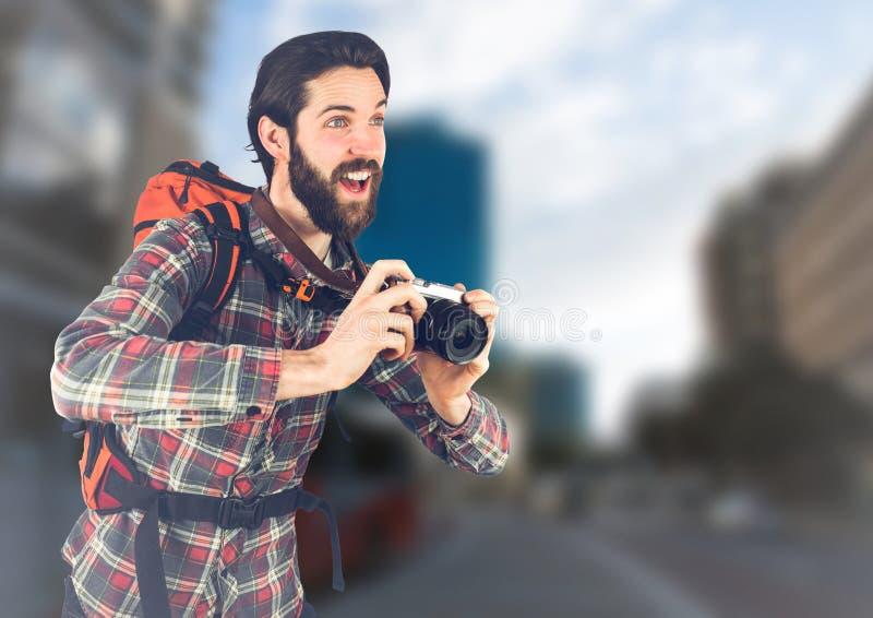 有照相机的千福年的背包徒步旅行者反对模糊的街道 免版税库存图片