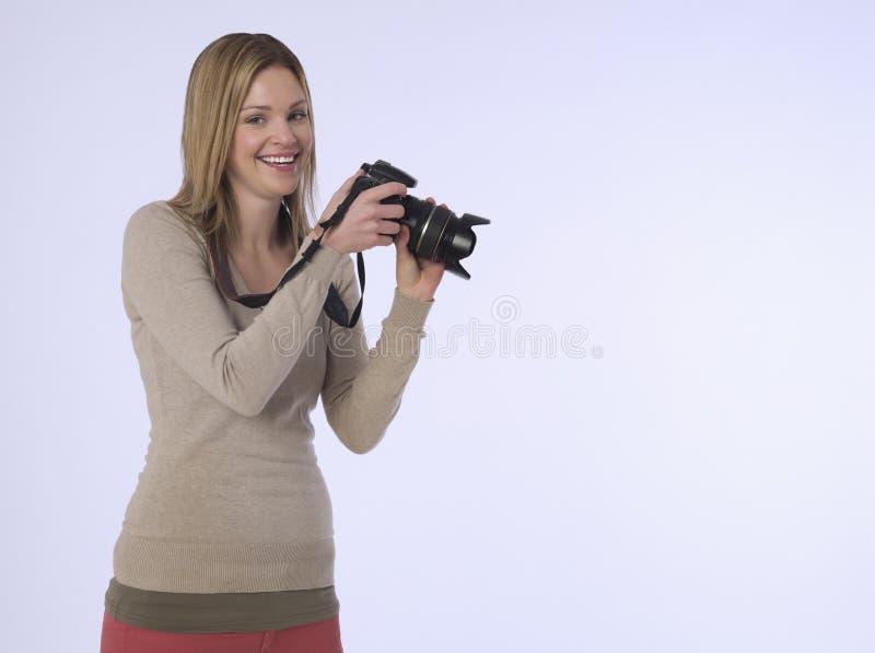 有照相机的女性摄影师在演播室 库存图片