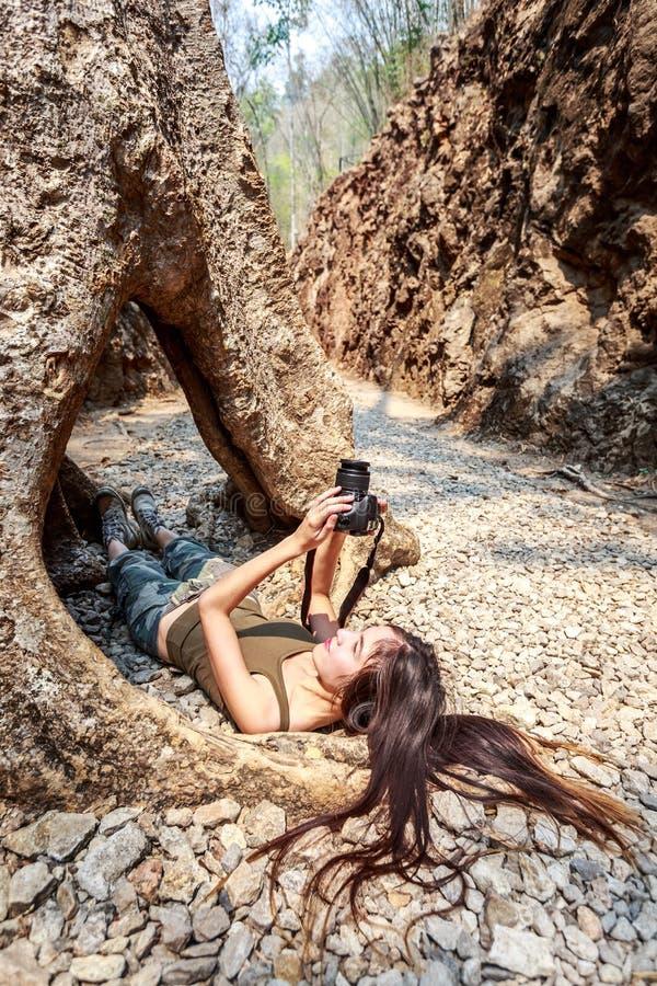 有照相机的妇女在树的孔躺下 库存图片