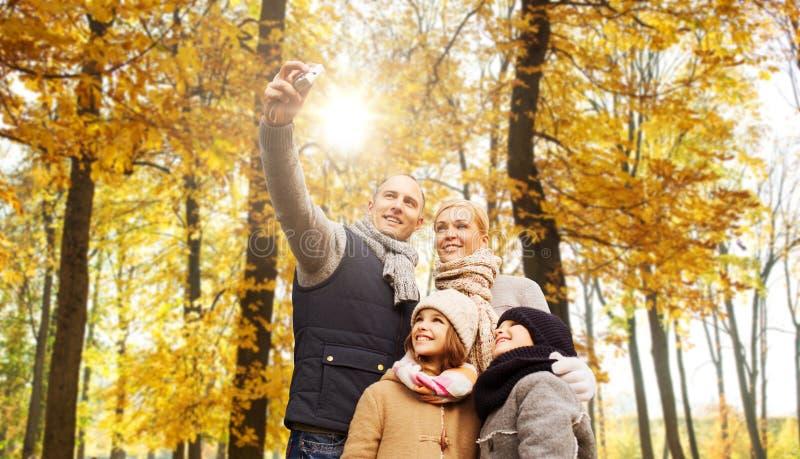 有照相机的幸福家庭在秋天公园 免版税库存图片