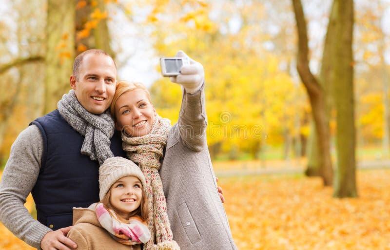 有照相机的幸福家庭在秋天公园 图库摄影