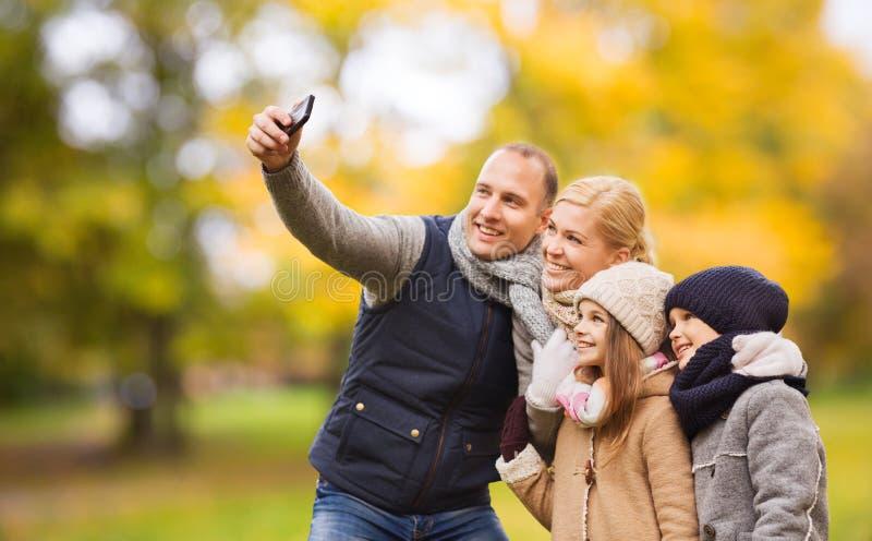 有照相机的幸福家庭在秋天公园 免版税库存照片