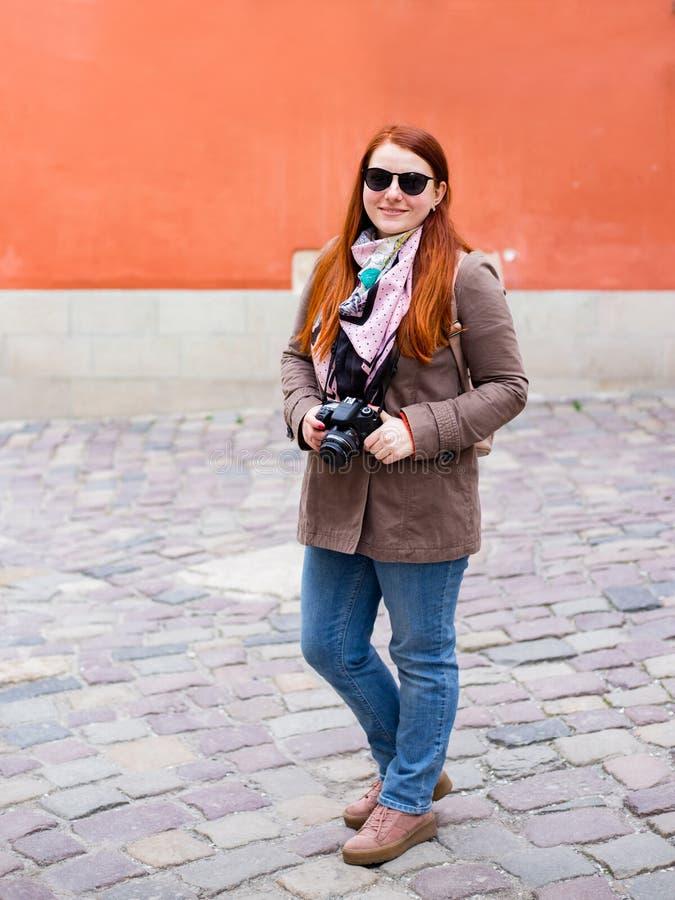 有照相机的旅行旅游妇女,样式太阳镜的红头发人女孩 库存图片