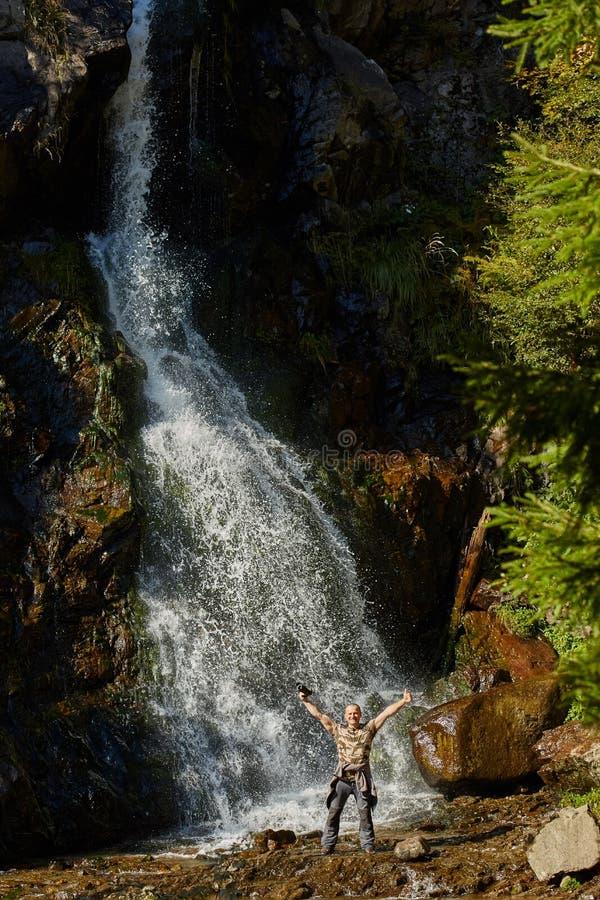 有照相机的游人在瀑布附近 免版税库存照片