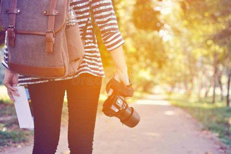 有照相机背包旅行和鞋子的妇女在自然概念tra 库存图片