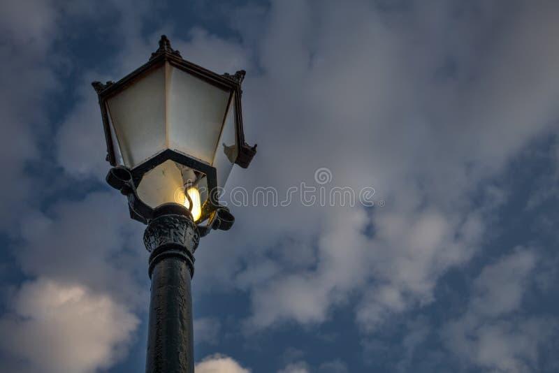 有熏制的玻璃和电灯泡的室外维多利亚女王时代的样式街灯 黑铁塑象唯一柱子向上看法  免版税库存照片