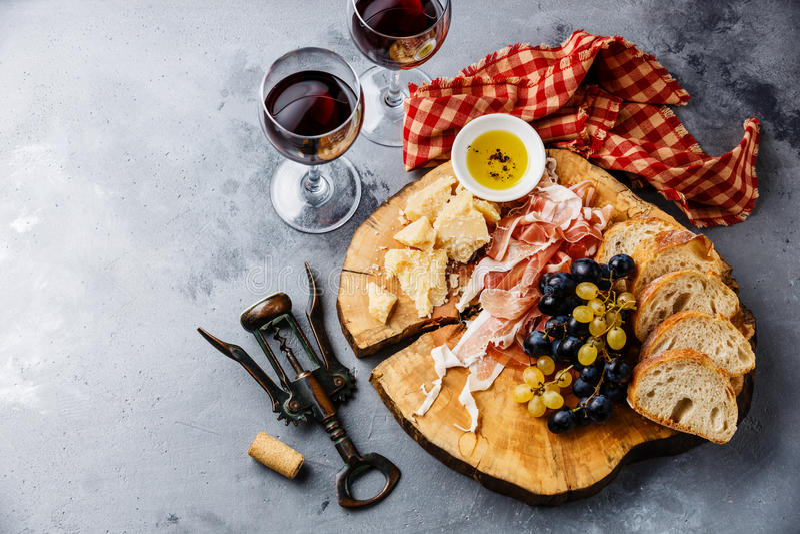 有熏火腿、乳酪、面包和酒的开胃菜板材 免版税库存图片