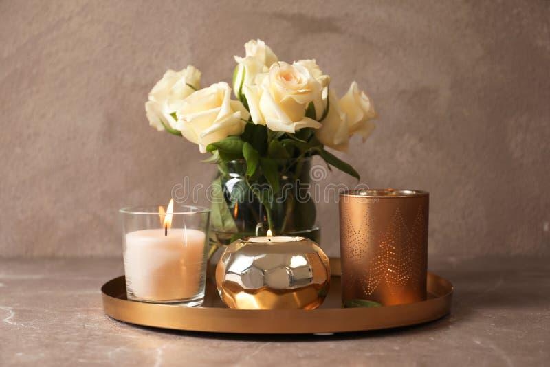 有燃烧的蜡蜡烛和花的盘子 免版税图库摄影