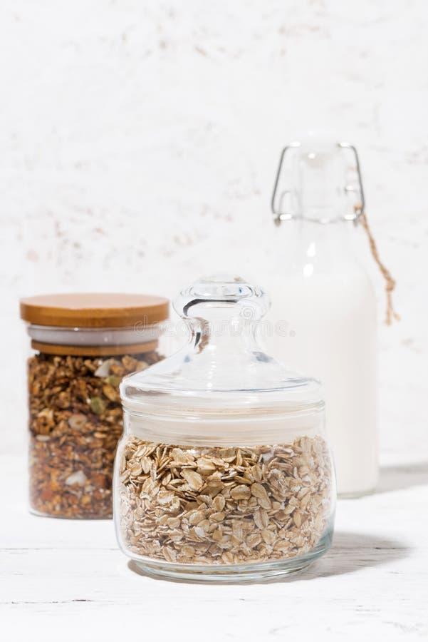 有燕麦剥落、格兰诺拉麦片和瓶的玻璃瓶子牛奶,垂直 免版税库存图片