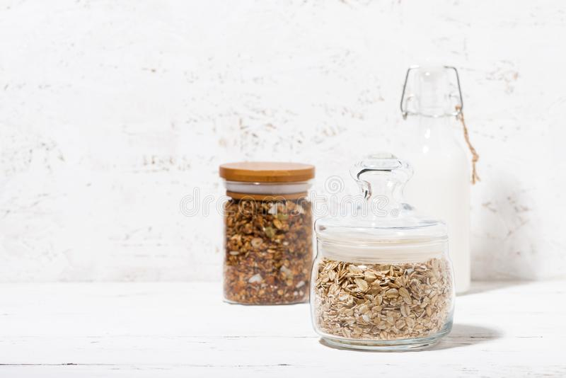 有燕麦剥落、格兰诺拉麦片和瓶的玻璃瓶子牛奶 免版税库存照片